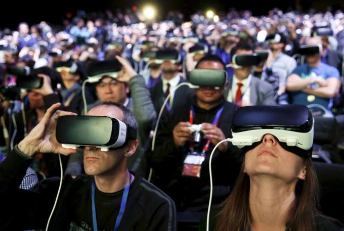 Посетители выставки мобильной индустрии Mobile World Congress, которая проходит в Барселоне, Испания, смотрят презентацию новых смартфонов Samsung S7 и S7 edge в шлемах виртуальной реальности Samsung Gear VR, 21 февраля 2016 года.