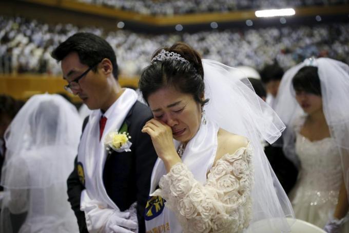 Невеста расплакалась во время церемонии массового бракосочетания, которая проводилась Церковью Объединения в Капхёне, Южная Корея, 20 февраля 2016 года.