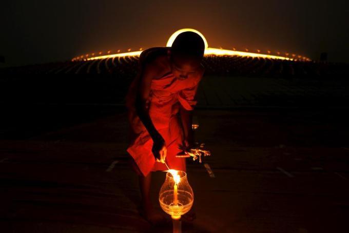 Буддистский монах зажигает свечу возле храма Ват Пхра Дхаммакая во время празднования Макха Бучи в провинции Патхумтхани в Таиланде, 22 февраля 2016 года.