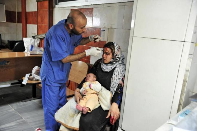 Врач оказывает медицинскую помощь женщине, получившей ранения во время бомбардировки южной части Дамаска, Сирия.